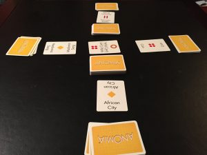 This is what the table looks like in a 4-player game of Anomia.  Notice that two players have cards with yellow diamonds on them; that means one player must name...